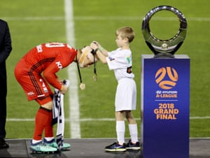 Lawrence Thomas of Melbourne Victory receives his winners medal after the A-League Grand Final.
