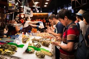 Tourists sampling food at Barcelona's Boqueria Market.