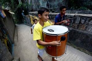 Brazilian kids walk through narrow hillside streets beating a drum on their way to the Favela Brass band rehearsals in Pereira da Silva favela