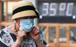 A lady adjusts her face mask in the 35C heat