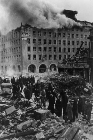 Citizens of Hamburg going about their business in the streets, surrounded by bomb sites and a wrecked building with smoke still pouring from it in about 1943
