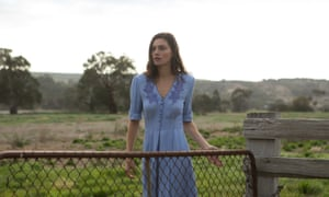 Phoebe Tonkin in a blue dress standing at a gate in front of a green paddock in the country