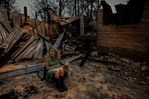 """Natalie Handsjuk and Mickey sit in the remains of Phoebe's Cottage. The quaint mudbrick house was named and built in memory of her daughter Phoebe. """"It seems symbolic, 10 years after her death, the decade ends with fire. The next cottage might just be called Phoenix."""""""