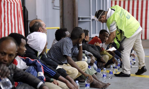 A doctor checks migrants aboard the Mare Nostrum after being rescued 25 miles off Italy.