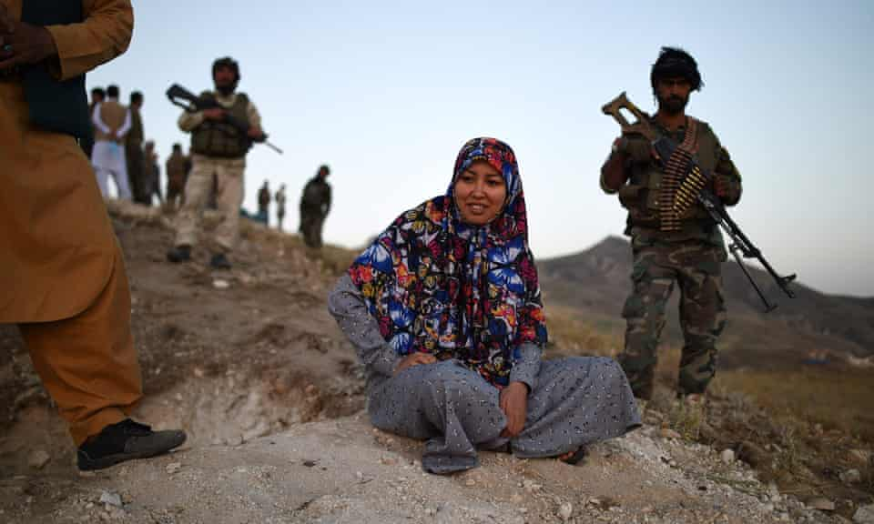 Salima Mazari sits on a hill observing the frontline against the Taliban surrounded by armed men.