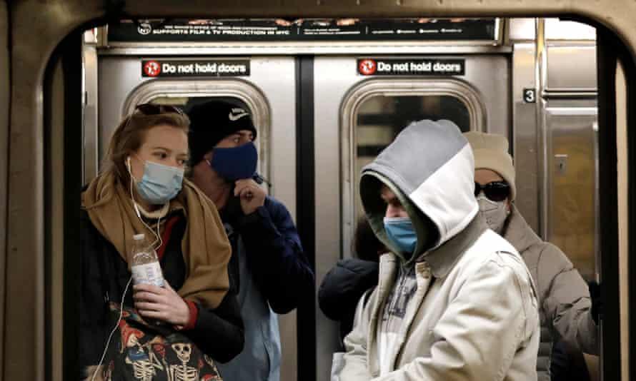 New York subway riders wearing masks. Fourteen states and Washington DC have universal masking policies.
