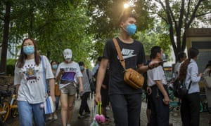 People wearing face masks to protect against the coronavirus walk along a street in Beijing, Friday, 31 July 2020.