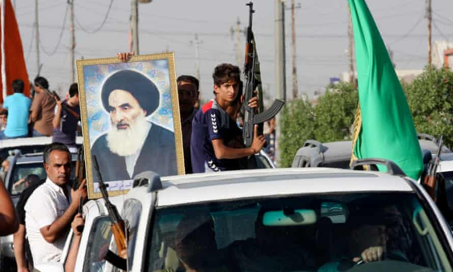 Iraqi army volunteers hold a picture of Ayatollah Ali Sistani in Sadr City, Baghdad