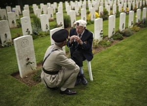 A World War II veteran talks to a soldier at the end of a ceremony to mark the 75th anniversary of D-Day at the Bayeux War Cemetery in Bayeux