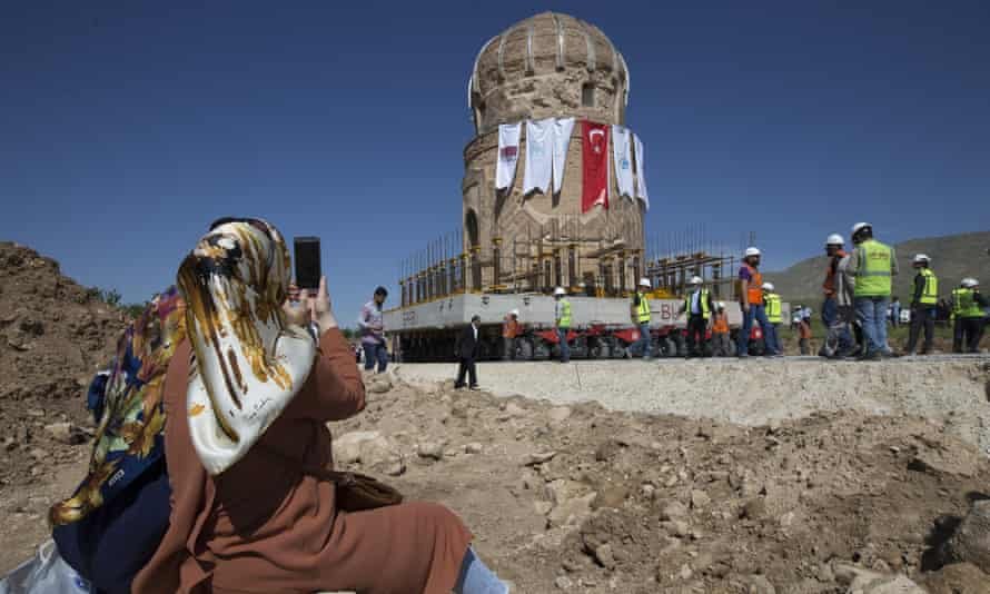 A woman films the relocation of the Zeynel Bey tomb.