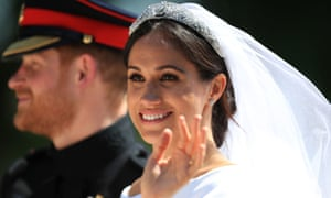 Prince Harry and Meghan Markle ride in a horse-drawn carriage after their wedding.