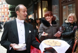Harrods butlers serve mince pies, tea and coffee to queuing shoppers.