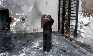 Two girls hug in the destroyed school gym in Beslan.