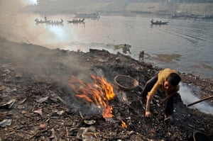 Standing on a mound of debris, a boy burns garbage to expose discarded scrap metal on the banks of the Buriganga river in Dhaka, Bangladesh. Once the garbage cools, he will use a magnet to collect the metal objects. Waste that cannot be recycled further is then disposed in the already heavily polluted river.