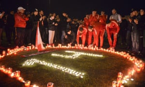 Dinamo Bucharest players light candles along with supporters for team-mate Patrick Ekeng, who died after collapsing during a league match on Friday.