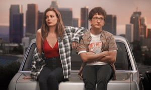 Gillian Jacobs and Paul Rust sitting on a car bonnet together in a scene from the romcom Love