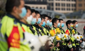 Chinese policemen wear protective masks during a national mourning to mourn victims of Covid-19 on 4 April, 2020 at Shanghai People's Heros Memorial Tower in Shanghai, China.