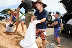 Jack Deyes helps his family to fill up sandbags in preparation for Cyclone Debbie in Townsville on Sunday.
