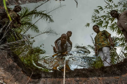 Sonny Olulu (centre), a youth leader in Kegbara Dere, Niger delta, and other members of the community look at a containment pond full of oil in a local swamp