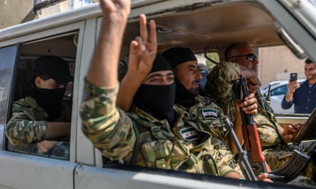 Turkish-backed Syrian opposition fighters drive towards the Syrian border.
