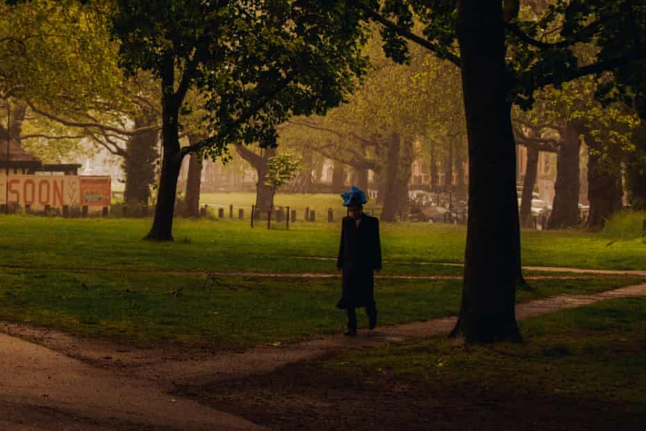 A man walks through Clapton Common wearing a plastic bag to protect his hat from the rain