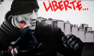 A man walks in front of a mural in Paris depicting Christophe Dettinger