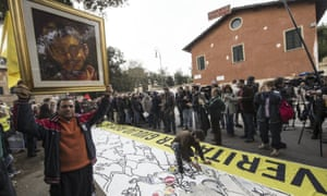 A man holds up a portrait of Giulio Regeni as people stage a sit-in outside Egypt's embassy in Rome