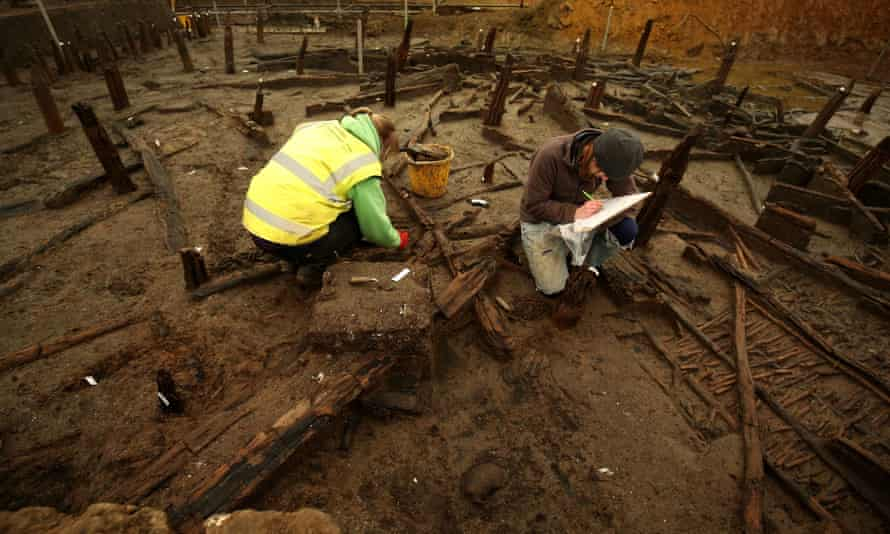 Archaeologists work on uncovered timbers.