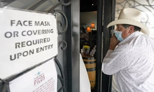 Sergio Almaguer wears a mask as he enters a restaurant in Houston. Texas has dropped its mask mandate, but many businesses continue to require them.