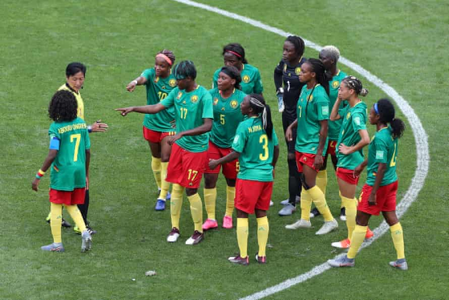Irate Cameroon players surround referee Qin Liang during a Round Of 16 match between England and Cameroon at Stade du Hainaut.