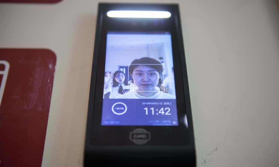 A woman uses a facial recognition device installed at an IFuree Go self-service supermarket in Tianjin