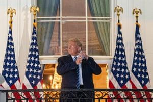 President Trump takes off his mask on a balcony of the White House