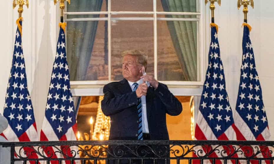 Donald Trump takes off his mask after returning to the White House on 5 October last year, following several days in hospital with Covid.