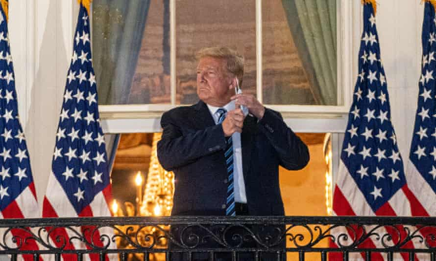 Donald Trump removing his mask on the White House balcony