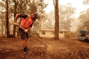 Sarsfield resident Wayne Johnston rakes leaf litter around his property