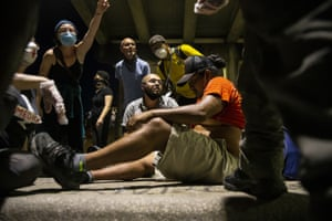 People help a protester after he was shot with a rubber bullet under interstate 35 freeway in Austin, Texas