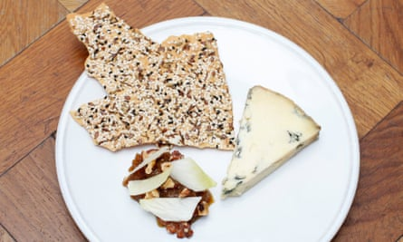 Triangular slice of Stichelton cheese with broken seeded flatbreads and sticky-looking chicory and walnuts