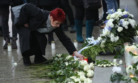 A mourner lays a candle at a memorial to victims of the attack.