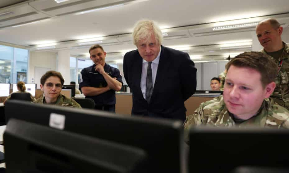 Boris Johnson watches operators behind monitors at the British Armed Forces' Northwood headquarters.