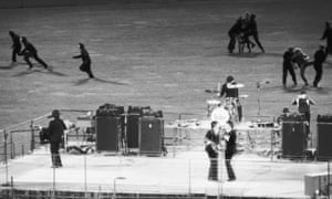 """""""Policemen clear the field of enthusiastic fans as The Beatles perform live"""""""