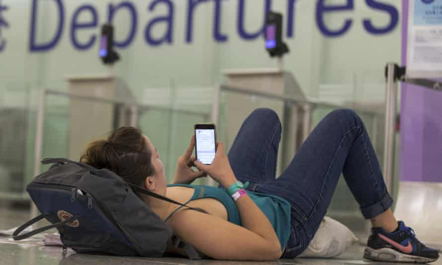 A traveller leans on her bag while browsing her smartphone