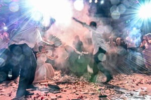 People dance to traditional Greek music amid broken plates during a wedding celebration in Athens.
