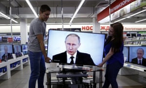Shop assistants install a TV at a electronics shop in Moscow.