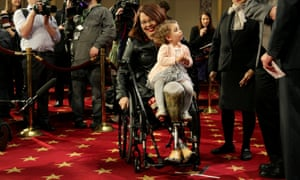 Senator Tammy Duckworth (D-IL) carries her daughter Abigail during the opening day of the 115th Congress on Capitol Hill in Washington.