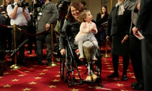 Duckworth carries her daughter Abigail during a mock swearing in with Vice President Joe Biden on Capitol Hill in 2017.