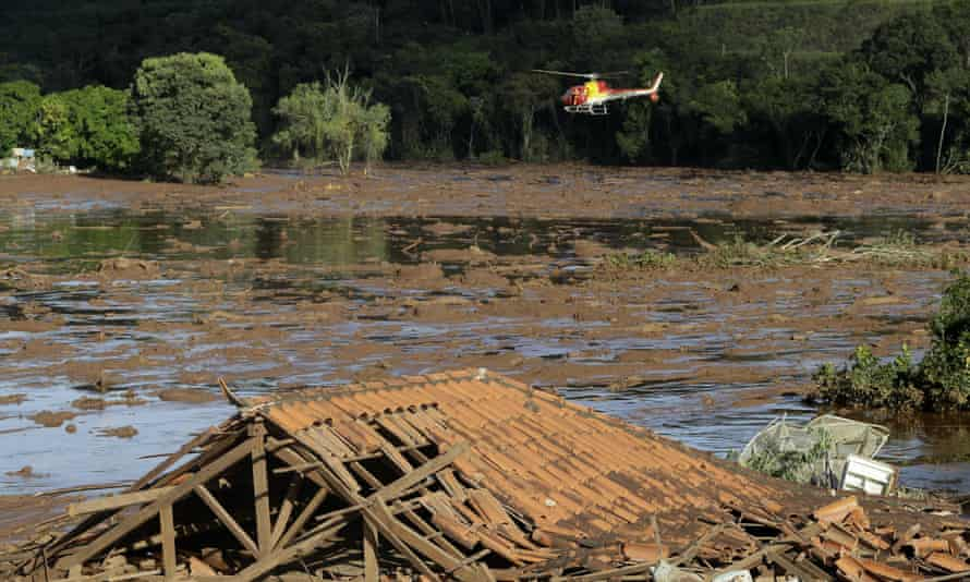 Rescue workers in a helicopter search a flooded area after a dam collapsed in Brumadinho, Brazil, on 27 January 2019.