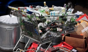 A supermarket trolley full of empty drinks bottles and cans awaiting