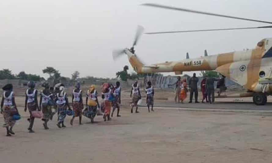 Some of the freed schoolgirls board a helicopter.