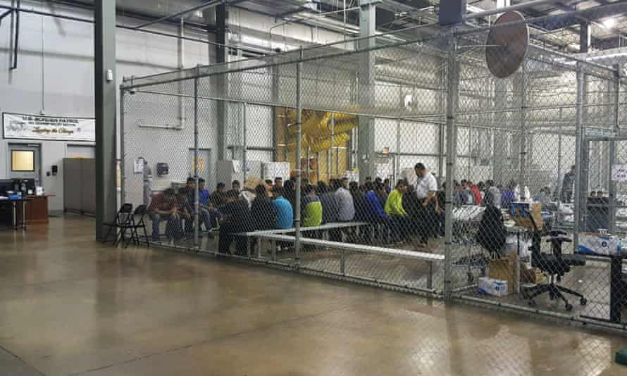 People who've been taken into custody related to cases of illegal entry into the United States, sit in one of the cages at a facility in McAllen, Texas, Sunday, 17 June.