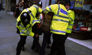 Police restrain a man in London. The Met police does not sanction the use of spit hoods.